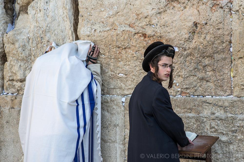 上图:哭墙晨祷。左边的男人披着祷告巾(Tallit Shawl),右手缠着经文匣(Arm Tefillin)。右边的男孩前额头上戴着经文匣(Head Tefillin)。经文匣里面藏着「示马」经文(申六4-9;十一13-21)。