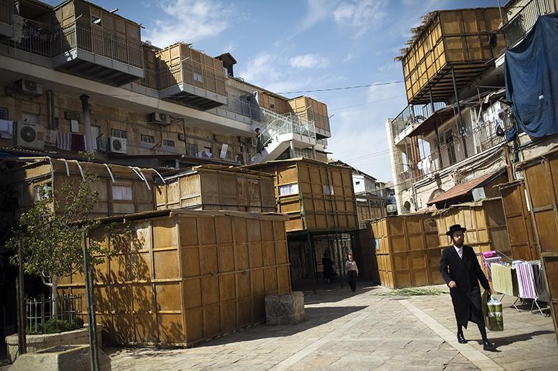 上图:2014年住棚节,一个犹太人走过耶路撒冷街道两旁的Sukkot棚子。