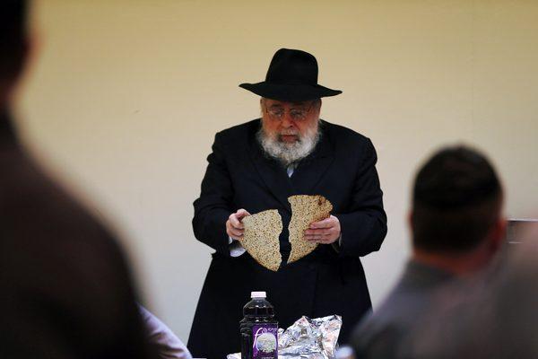 """上图:一位犹太人在逾越节晚餐的第一杯酒以后,把三块无酵饼中间的那块Yachatz掰开,其中大的一半称为Afikomen。这半块Afikomen要藏起来,等吃完苦菜、羊肉,喝第三杯酒之前让孩子去找出来。这半块无酵饼被掰开、藏起来、又被找到,岂不正指着主耶稣的受死、埋葬和复活吗?这半块无酵饼叫Afikomen,源于希腊文""""那将要来的"""",岂不正指着那将要来的弥赛亚主耶稣基督吗?"""