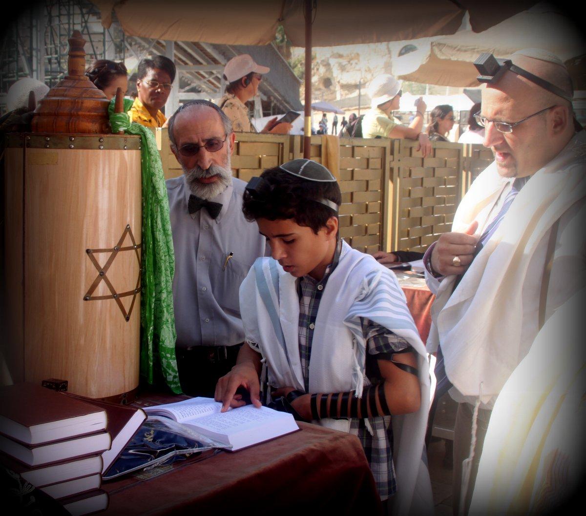 上图:一个犹太男孩在成为「诫命之子」的仪式上,他的前额和手上都带着经文匣(Tefillin),身上披着祷告巾( Tallit)。犹太儿童虽然被鼓励遵守诫命,但律法没有要求他们遵守诫命。当男孩到13岁,女孩子到12岁,就有责任遵守律法诫命,被称为「诫命之子」(Bar Mitzvah)和「诫命之女」(Bat Mitzvah)。男孩将承担更多责任,被安排在会堂中诵读妥拉、先知书和唱颂圣歌,带领聚会和公祷。