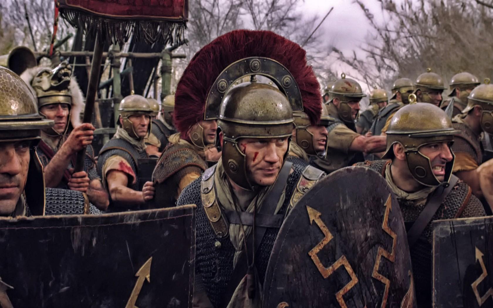 上图:百夫长是罗马军团中最重要的职业军官,平时负责训练,战时负责指挥。普通百夫长相当于今日的中尉,领导一个百人队,首席百夫长则相当于今日的上校。要想成为百夫长,必须获得数位重要人物的推荐信,年满30岁,具备读写能力,所以百夫长都具有良好的社会地位和丰富的经验,受教育程度比较高,连这样见多识广的百夫长都觉得主耶稣的死非常特别。百夫长的铠甲是银色的,短剑置于身体左侧而不是右侧,身体右侧可能放置匕首,腿上有护胫,他们执盾,穿旧式的锁子甲,在胸前或者其他显著位置佩戴奖章。百夫长最显著的标志是头顶上的马毛或羽毛装饰,与普通士兵不同,他们的饰板是横排而不是纵列。因为百夫长并身先士卒,而且服饰不同,所以百夫长在战斗中的伤亡率比普通士兵高得多。