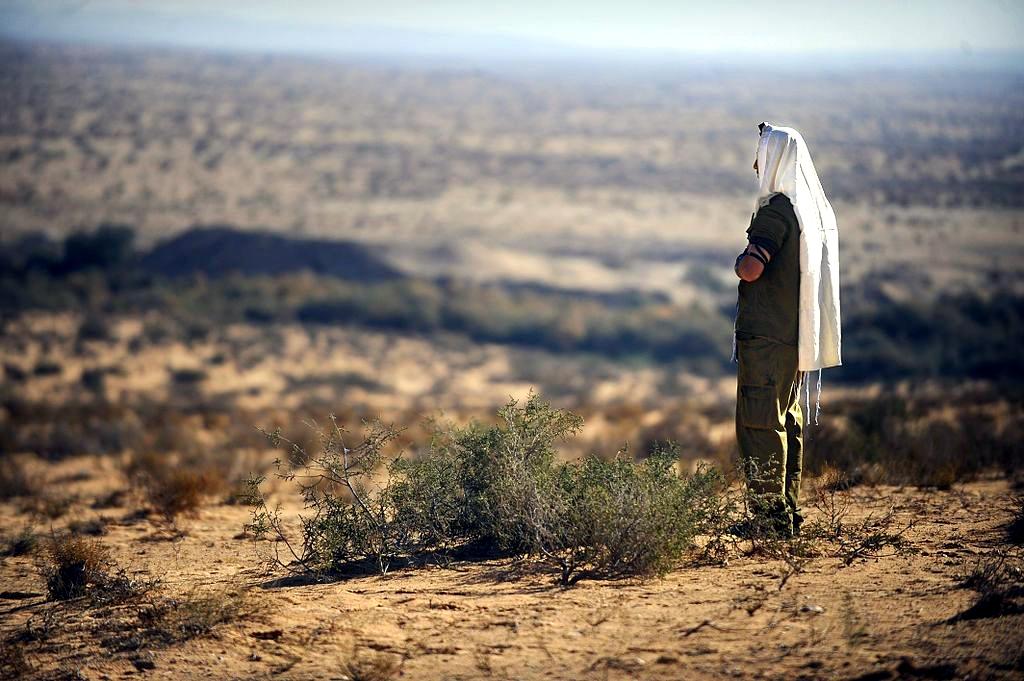 上图:一名以色列国防军士兵早晨向着耶路撒冷的方向祷告。