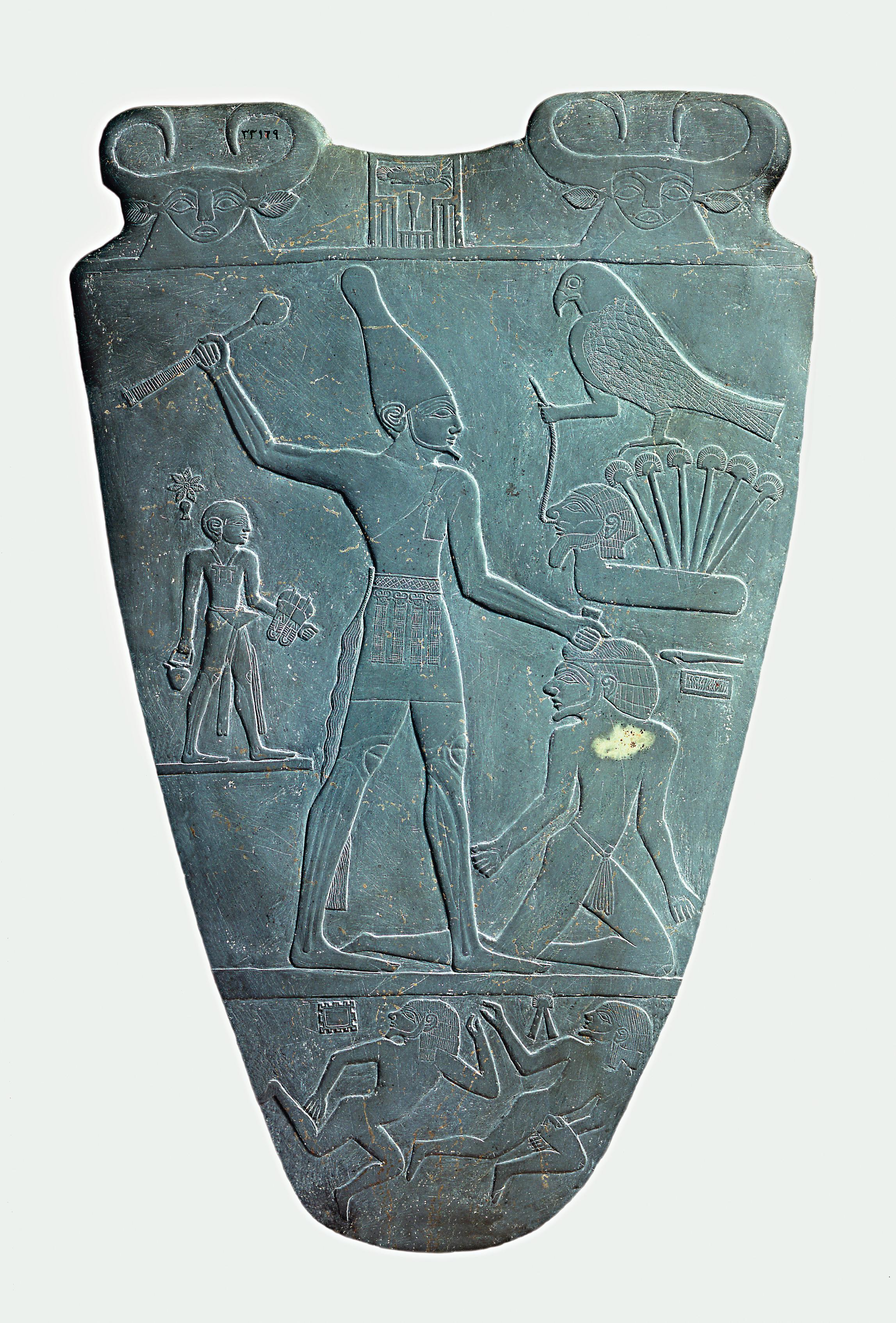 上图:主前31世纪的纳美尔石版(Narmer Palette)的正面,描绘统一了上下埃及的纳美尔头戴上埃及王冠,正要用权杖打破敌人的头,这个姿势后来成为埃及表现征服者的经典艺术形象。纳美尔石版是一个双面盾形的浮雕石板,一面描述戴着上埃及王冠的纳美尔,另一面描绘了戴着下埃及王冠的纳美尔,现藏于埃及开罗博物馆。