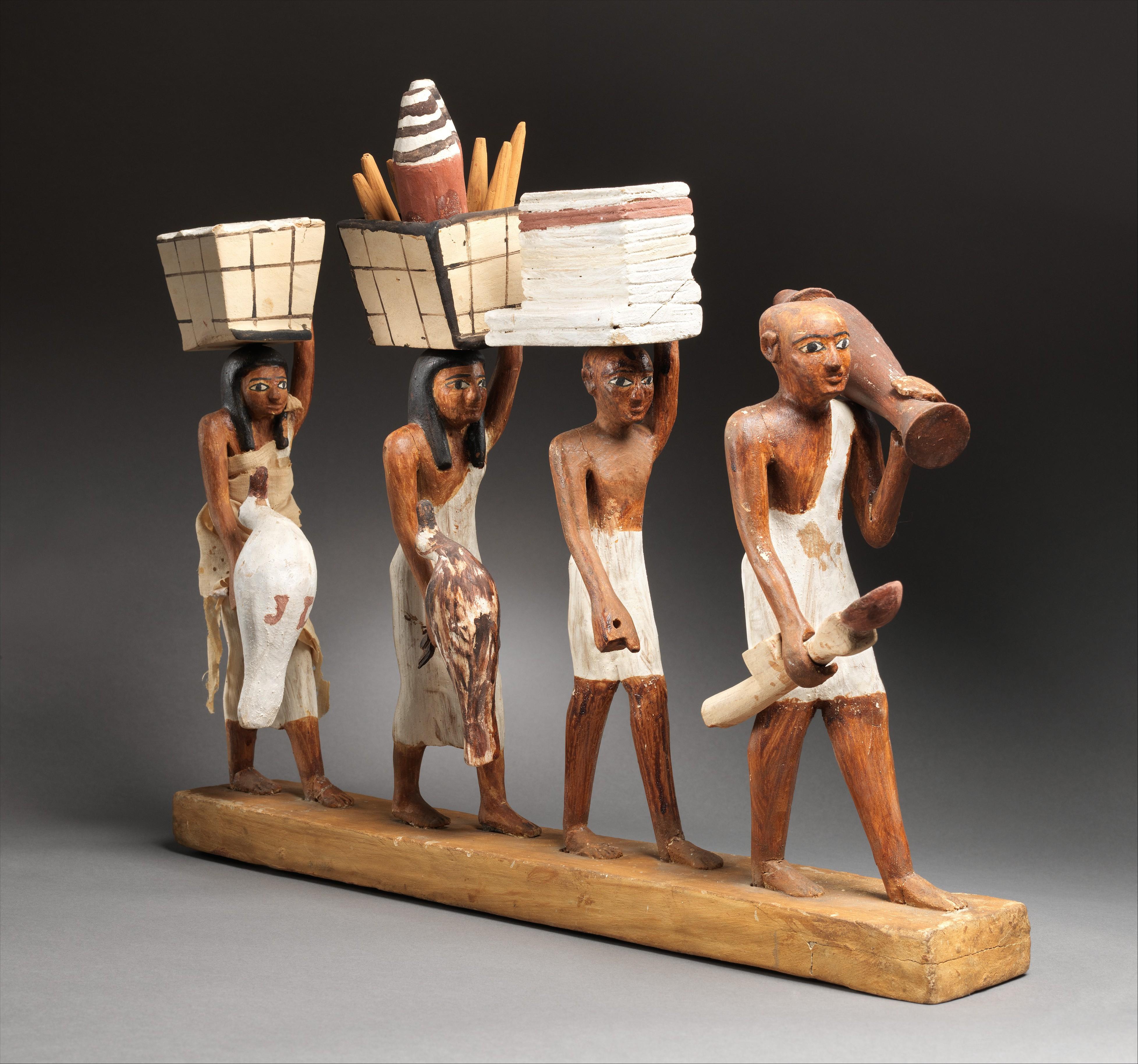 上图:主前1981-1975年古埃及墓葬里一队头顶食物的仆人木偶。现藏于纽约大都会艺术博物馆。