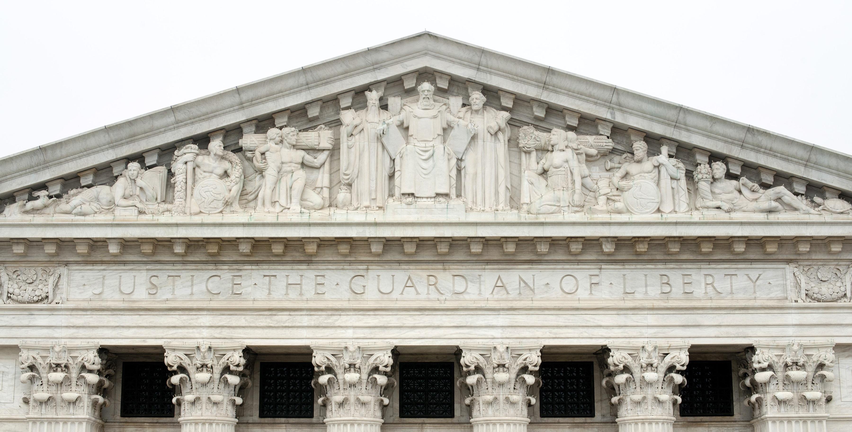 上图:华盛顿特区美国最高法院大楼东门上方的浮雕,中间是拿着两块十诫石版的摩西,左边是孔子,右边是梭伦。