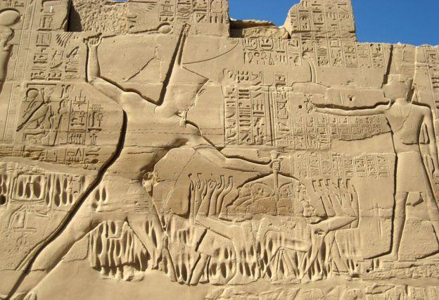 上图:埃及底比斯卡纳克神庙(Karnak Temple)的米吉多战役浮雕,描绘图特摩斯三世(Thutmose III,主前1479-1425年在位)一手抓住一群迦南俘虏的头发,一手在施行惩罚。「手」在古代中东常被用来比喻君王的能力和军事力量。