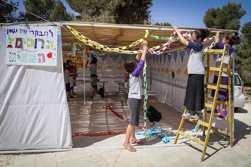 上图:几个犹太女孩正在装饰住棚节(Sukkot)的棚子。这棚子只有三面墙,通常用树枝和秋果来布置。犹太人被掳巴比伦回归之后,以斯拉吩咐各人用「橄榄树、野橄榄树、番石榴树、棕树和各样茂密树的枝子」在自己的房顶上、院内或城中宽阔处搭棚(尼八15-18)。住棚节犹太人还要在会堂诵读传道书。
