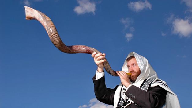 上图:一个犹太人于犹太新年吹响公羊角制成的羊角号(shofar)。犹太人被掳巴比伦回归以后,吹角节成为犹太人的农历新年(Rosh Hashanah),这一天要一百次吹响羊角号。