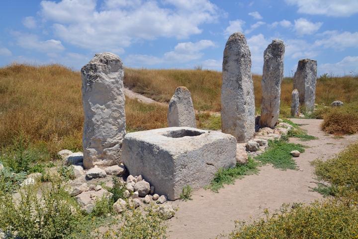 上图:考古学家在基色迦南人的圣所中发现了十根石柱,方石墩上的圆孔可能是用来立「木偶」的。在迦南宗教中,石柱代表生殖崇拜中的男神,被称为「柱像」。树木代表女神,被称为「木偶」或「亚舍拉柱」。男神和女神的名字及和相互之间的关系,不同地方的迦南人有不同的说法。男神的名字通常是「巴力 Baal),但不同的地方又有地方特色,如「巴力·毗珥」、「巴力·比利土」、「巴力·西卜」,统称「诸巴力 Baals」。女神的名字有的地方叫「亚纳特 Anath」、有的地方叫「亚舍拉 Asheroth」、有的叫「亚斯她录 Ashtaroth」,有的地方认为她是巴力的妻子、有的地方认为她是巴力的母亲。