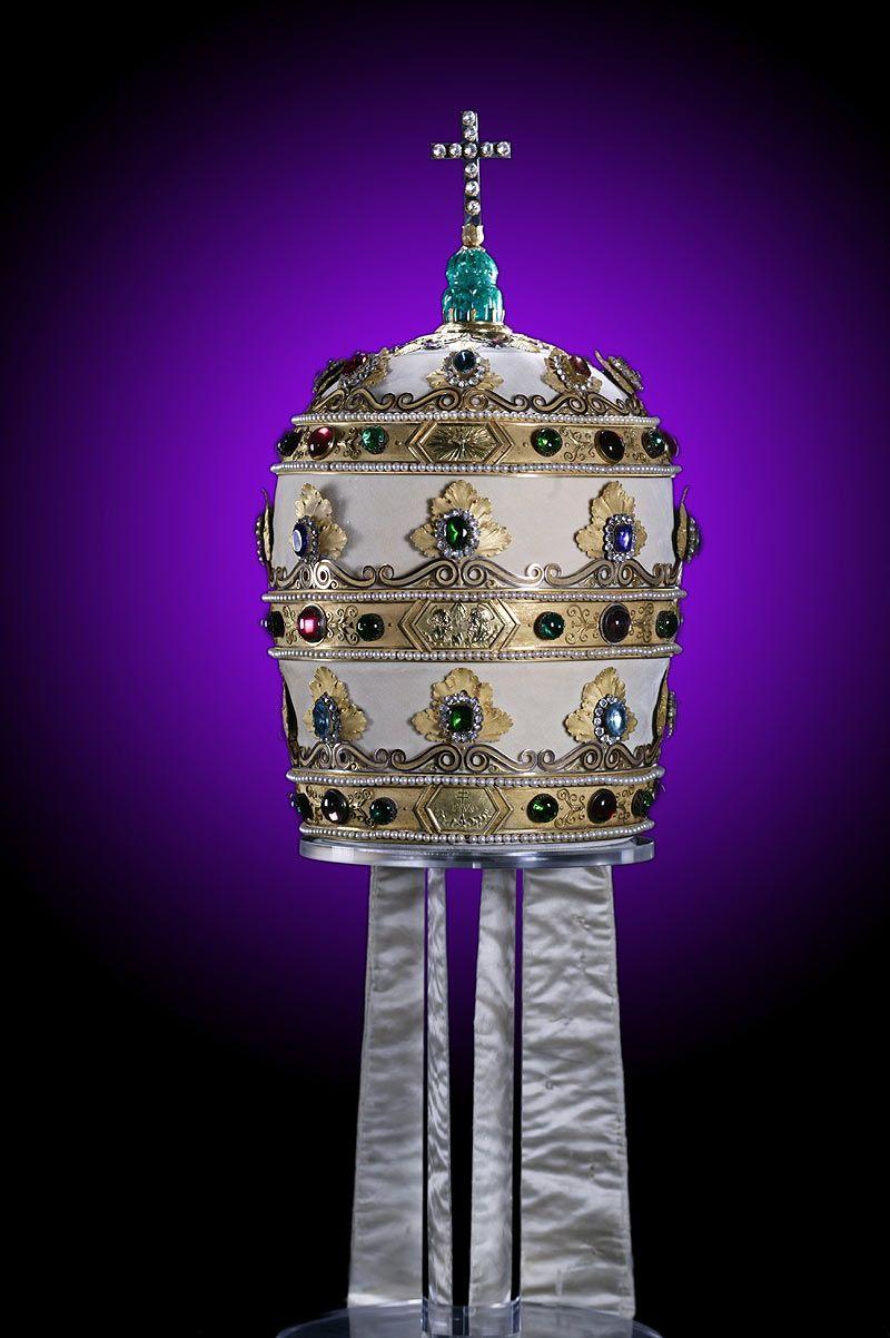上图:拿破仑三重冕(Napoleon Tiara),是拿破仑于1805年送给教宗庇护七世的三重冕(Triregnum),虽然用珠宝装饰得非常华丽,却故意做得又小又重,难以佩戴。每道箍的中间原来都有一个美化拿破仑的浮雕,后来被圣经经文所取代:上层是徒二十28,中间是启十一4,底层是诗八十五10。 教宗本笃十五世卖掉头饰的珠宝为一战受难者筹款,代之以玻璃复制品。