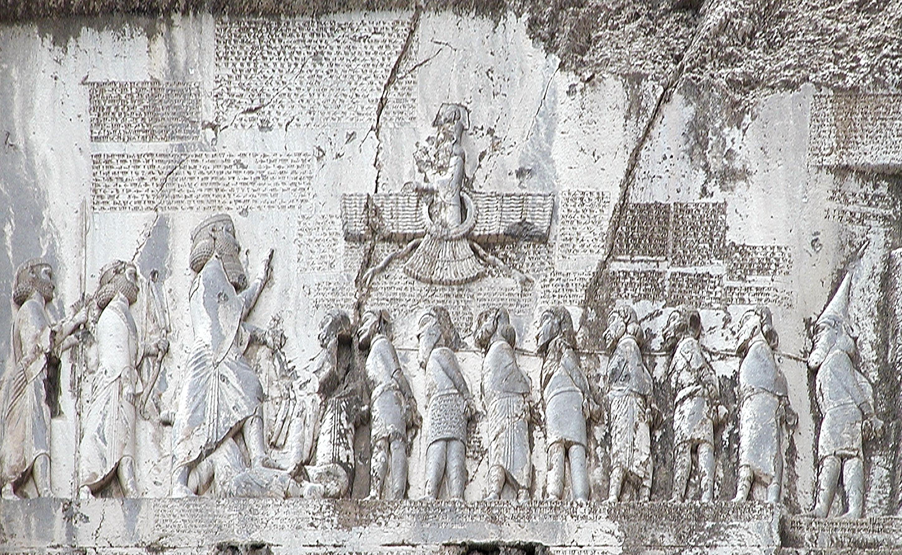 上图:贝希斯敦铭文(Behistun Inscription)是刻在伊朗贝希斯敦山崖上的多语言铭文,由波斯阿契美尼德帝国大流士一世所立,记录了他镇压高墨达(Gaumata)政变和各地反叛、取得王位的经过。石刻上有描绘大流士一世脚踏高墨达的浮雕,周围的铭文以三种不同的楔形文字写成:古波斯语、亚兰语和巴比伦语。这个石刻有如罗塞塔石碑之于埃及象形文字一样,极大地帮助了专家们破解楔形文字。1835年,英国人罗林森(Sir Henry Rawlinson)拓取了石刻上的古波斯文铭文,1844年又拓取了其余的铭文。在他和其他学者的努力下,古波斯文铭文首先被成功解读,其它两种铭文随后也被成功解读。