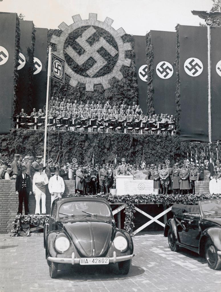 上图:1938年6月25日,希特勒在沃尔夫斯堡参加大众汽车厂的奠基仪式,前面是一辆大众甲壳虫汽车。希特勒上台后不久,就要求生产一种普通德国人买得起的「人民汽车」,可容纳2名成人和3名儿童、最高时速可达100km/h、最好采用风冷发动机,只卖990马克。奥地利工程师费迪南德·保时捷根据这一要求设计出著名的大众甲壳虫汽车。1936年10月12日,三辆大众VW-1下线。1938年,大众汽车公司在沃尔夫斯堡建厂,计划年产150万辆。二战期间,大众的生产能力被用于军备生产。德国人民所盼望的好处,最后都归于无有。正如圣经对大淫妇的预言:「你所看见的那十角与兽必恨这淫妇,使她冷落赤身,又要吃她的肉,用火将她烧尽」(启十七16)。兽其实并不喜欢大淫妇,只是暂时利用大淫妇迷惑世人。当大淫妇的价值被榨取干净之后,就会被付之一炬。