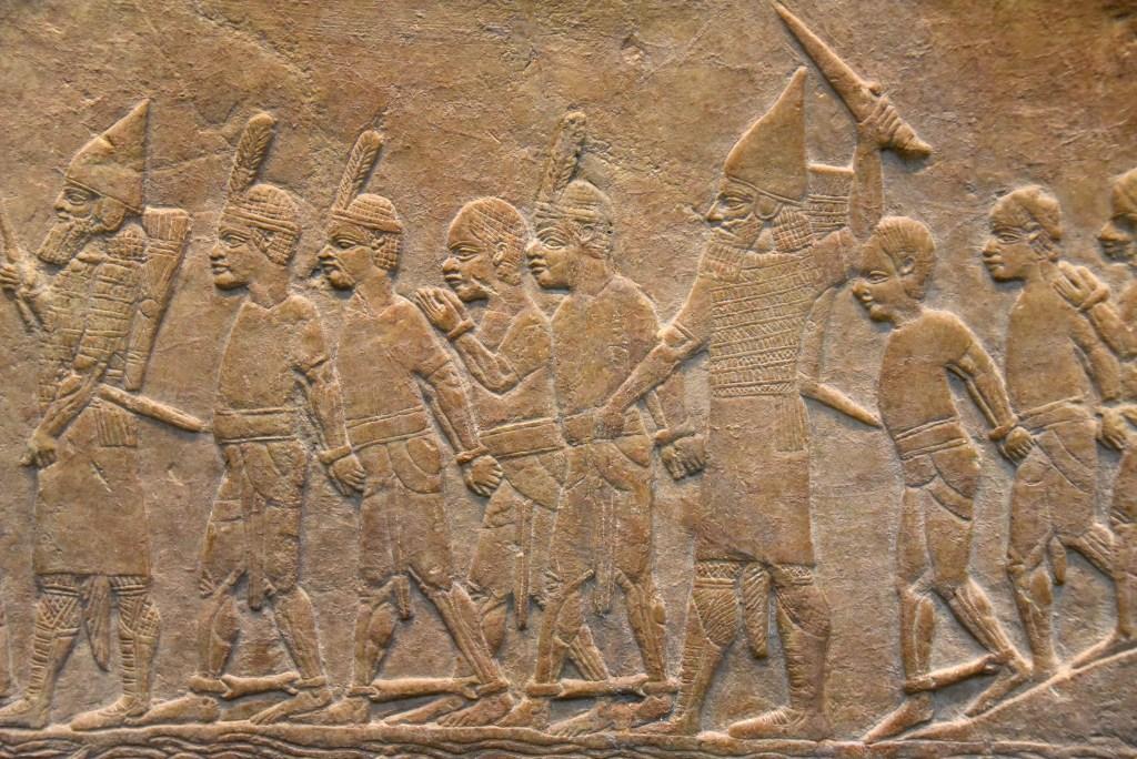 上图:主前645-635年从尼尼微出土的亚述浮雕,描绘主前667年亚述袭击埃及孟斐斯的一座堡垒,第二十五王朝法老特哈加(Taharqa)的古实士兵穿着短裙、赤着脚,被戴上手铐和脚镣掳走。收藏于大英博物馆。