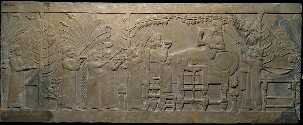 上图:尼尼微出土的主前645-635年的亚述浮雕,展现了古代美索不达米亚的精致家具,现藏于大英博物馆。画面中的亚述王亚述巴尼拔斜靠在葡萄架下的沙发上,武器放在身后、王后坐在对面的椅子上,正在愉快地享受美酒和点心。拿着餐巾的女仆们为他们扇风,男仆们为他们带来食物和音乐,鸟儿和蝗虫在树上安歇,而最左边的树上可怕地挂着以拦王的头颅。